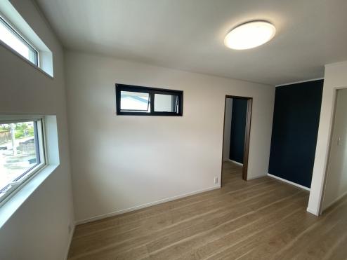 主寝室にはデザイン性の高いワイドな窓を配置しているので明るさは十分。 書斎のある吹き抜け部分とリンクする黒い壁紙が部屋全体を引き締め落ち着いたプライベートスペースに。 また開閉可能な小窓が吹き抜けと繋がっているのもおもしろい。
