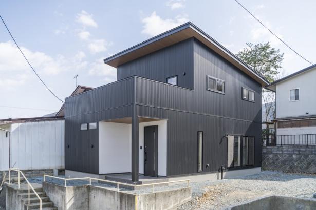 ガルバリウム鋼板の外壁と、白壁の組み合わせ。軒天は木目調のニチハ軒天12